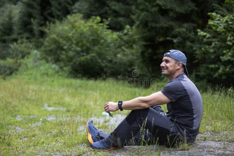 Szczęśliwy rozważny marzycielka mężczyzna siedzi na zielonej trawie w pa fotografia stock