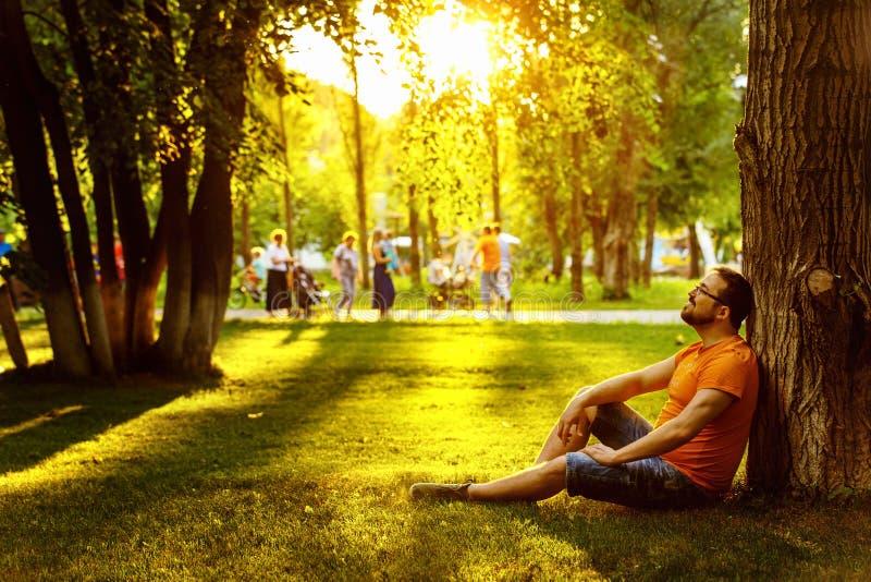 Szczęśliwy rozważny marzycielka mężczyzna siedzi na zielonej trawie w parku obraz royalty free