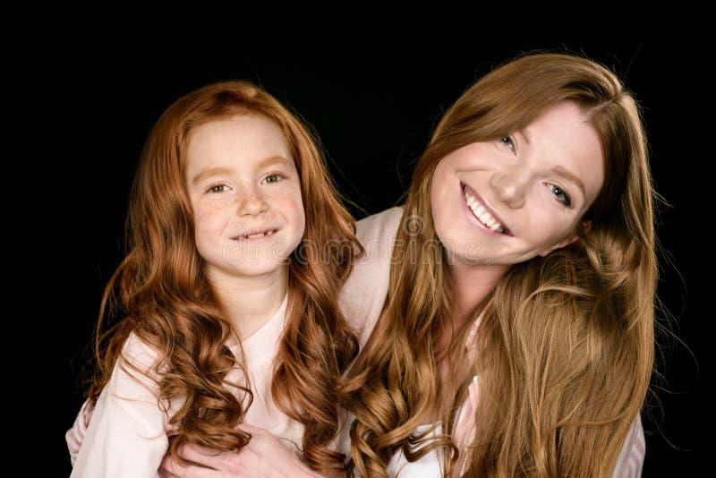 Szczęśliwy rudzielec córki i matki obejmowanie odizolowywający na czerni obrazy stock