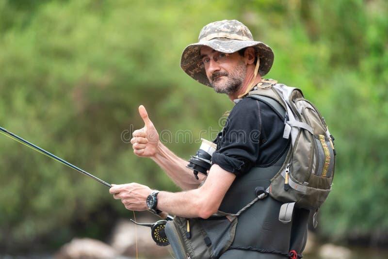 Szczęśliwy rybak z brodą na brzeg rzekim z połowu prąciem w jego rękach, seans aprobaty tw?j wakacje rodzinny szcz??liwy lato zdjęcie royalty free