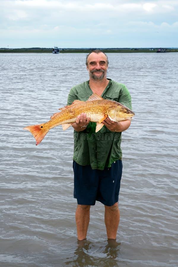 Szczęśliwy rybak z dużym złotym rybim Czerwonego bębenu Sciaenops ocella zdjęcie stock