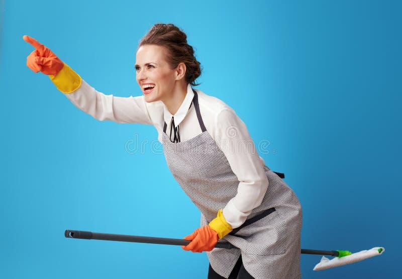 Szczęśliwy scrubwoman wskazuje przy coś używa kwacz jako broomstick fotografia royalty free