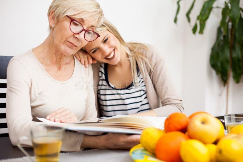 Szczęśliwy senior macierzysty i jej córka patrzeje rodzinnego album fotograficznego podczas gdy siedzący przy łomota stołem Córki fotografia royalty free