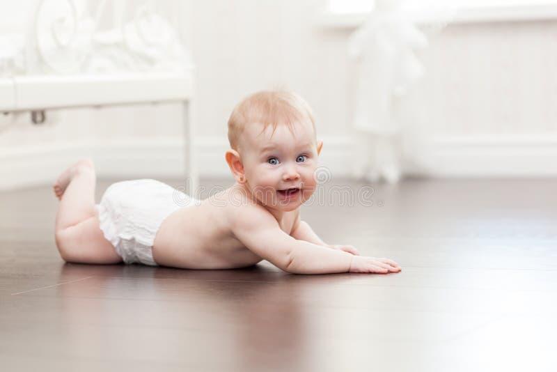 Szczęśliwy siedem miesięcy dziewczynki stary czołganie na twarde drzewo podłoga obrazy stock