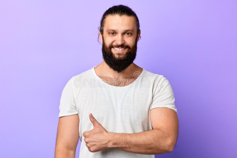 Szczęśliwy silny mięśniowy mężczyzna z promieniejącym uśmiechem pokazuje kciuk w górę zdjęcie royalty free