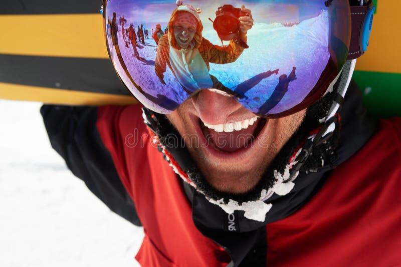 Szczęśliwy snowboarder w masce z przyjacielem bierze strzał w odbiciu zdjęcia stock