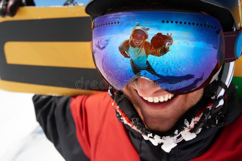 Szczęśliwy snowboarder w masce z przyjacielem bierze strzał w odbiciu fotografia royalty free