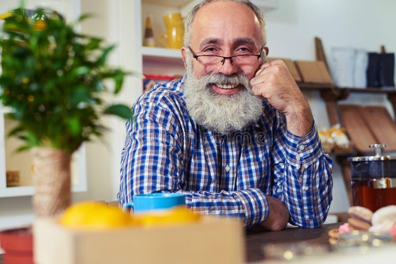 Szczęśliwy starszego mężczyzna obsiadanie przy stołem i opierać jego kierowniczego na th obraz royalty free