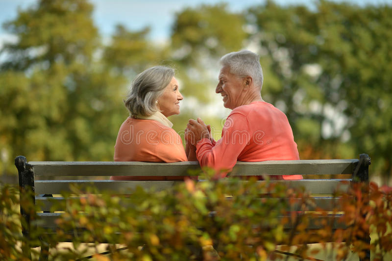Szczęśliwy starszej osoby pary obsiadanie na ławce obrazy stock