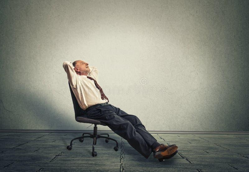 Szczęśliwy starszy biznesowy mężczyzna relaksuje w pustym biurze zdjęcie stock