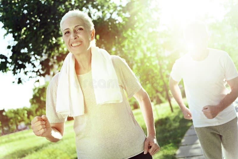 Szczęśliwy starszy kobiety biegać szybki niż jej mąż obraz stock