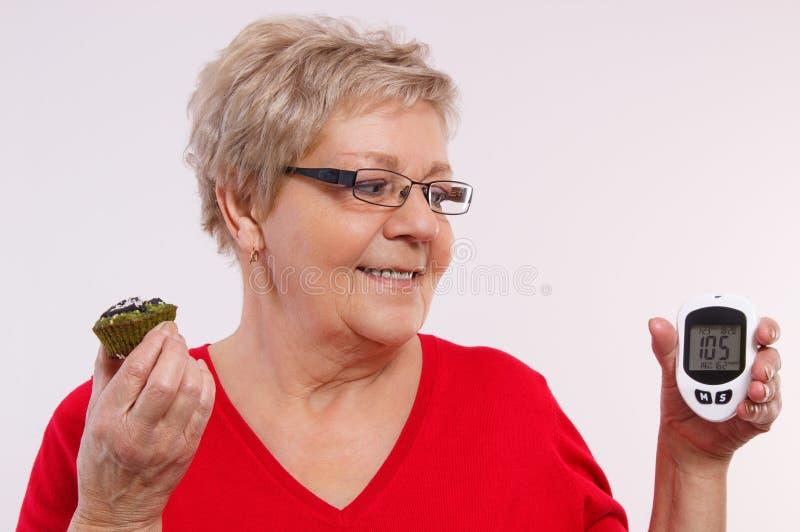 Szczęśliwy starszy kobiety mienia glucometer, świeża babeczka i, pojęcie cukrzyce fotografia royalty free