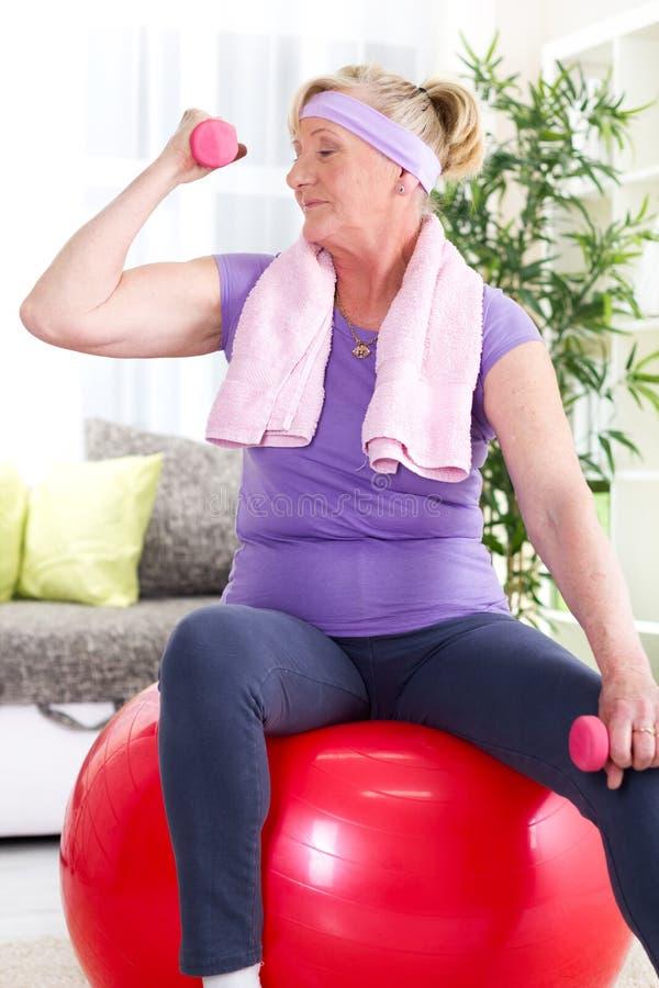 Szczęśliwy starszy kobiety obsiadanie na gym piłce i ćwiczenie z dumbbe, zdjęcie stock