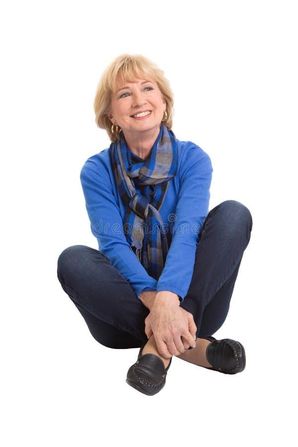 Szczęśliwy starszy kobiety obsiadanie na podłoga odizolowywającej na białym tle fotografia stock