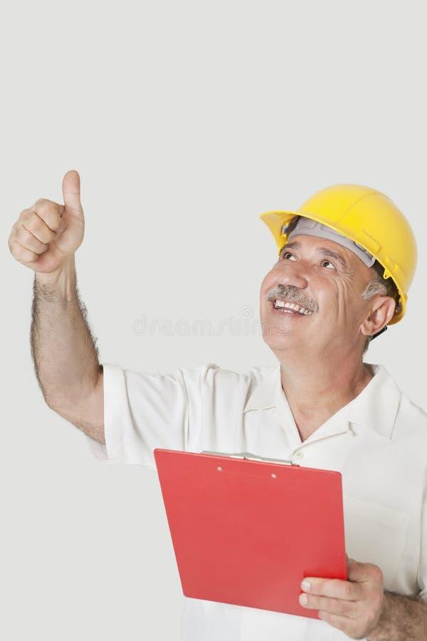 Szczęśliwy starszy konstruktora mienia schowek podczas gdy gestykulujący aprobaty nad szarym tłem obraz stock