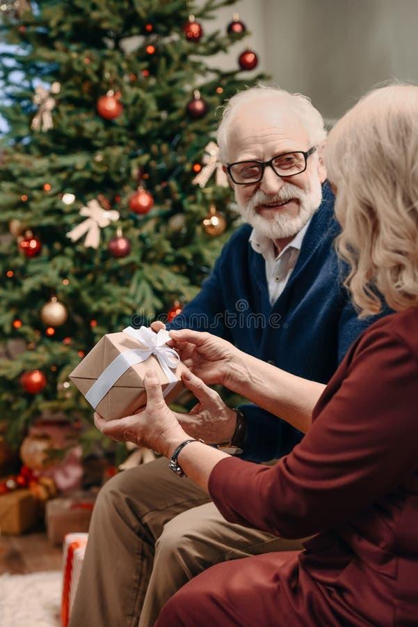 szczęśliwy starszy mężczyzna przedstawia boże narodzenie prezent żona przed pięknym obrazy stock
