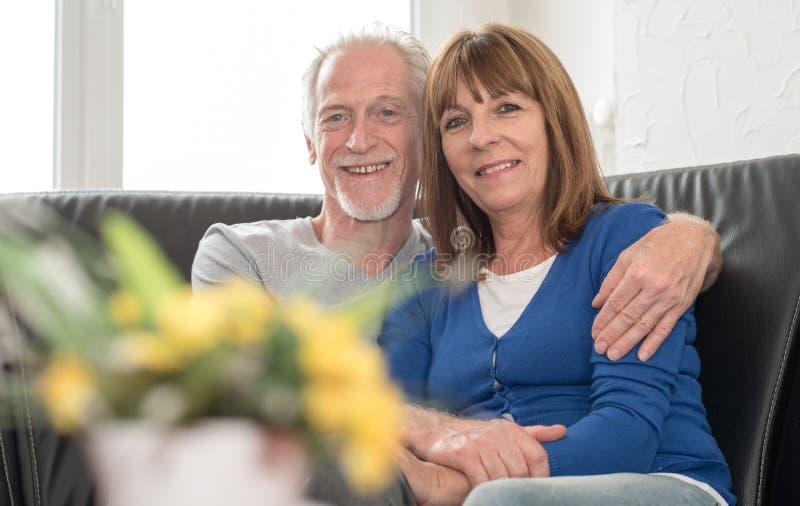 Szczęśliwy starszy pary obsiadanie na kanapie i obejmowaniu each inny zdjęcia royalty free