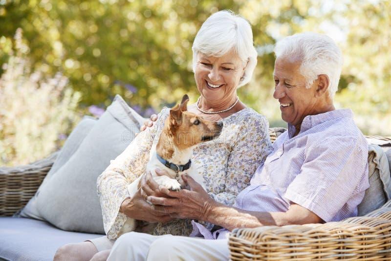 Szczęśliwy starszy pary obsiadanie z zwierzę domowe psem w ogródzie obraz stock