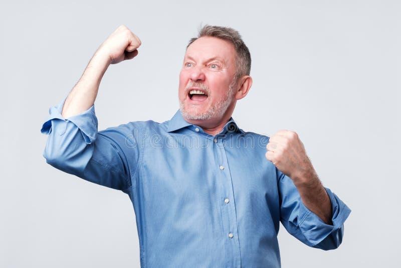 Szczęśliwy starszy silny mężczyzna, podnosi zaciskać pięści w gescie hooray, tryumfuje obrazy stock