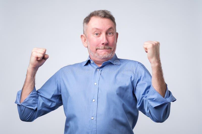 Szczęśliwy starszy silny mężczyzna, podnosi zaciskać pięści w gescie hooray, tryumfuje zdjęcia royalty free