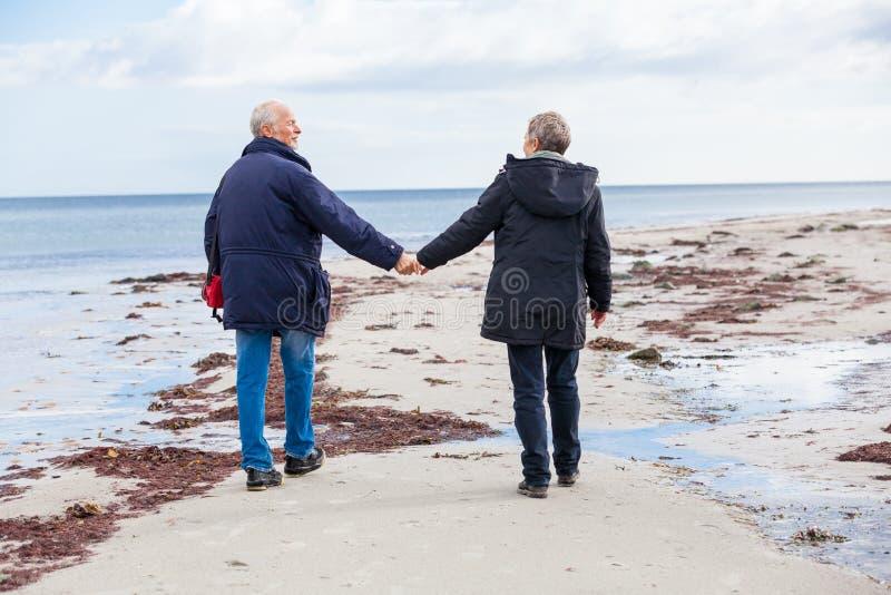 Szczęśliwy starszy starszy pary odprowadzenie na plaży zdjęcia stock