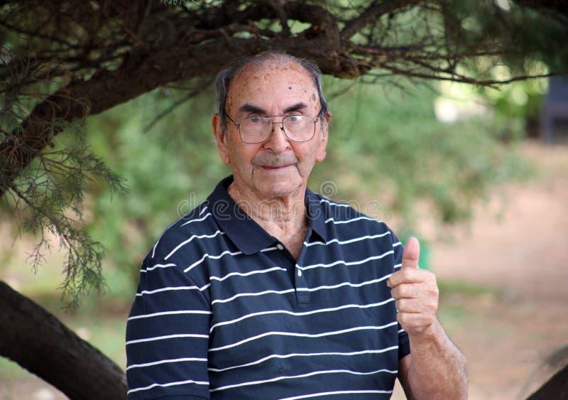 Szczęśliwy stary dziadek cieszy się życia falowanie z dużym uśmiechem, dużymi szkłami i ufnym abuelo cześć, zdjęcia stock
