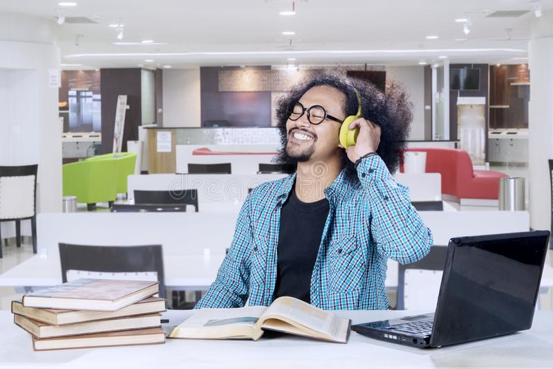 Szczęśliwy student collegu cieszy się muzykę podczas nauki obrazy royalty free