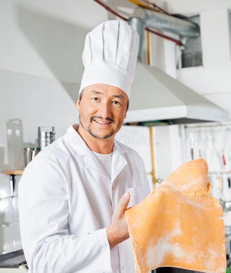 Szczęśliwy szefa kuchni mienia pierożka makaronu prześcieradło W kuchni fotografia royalty free