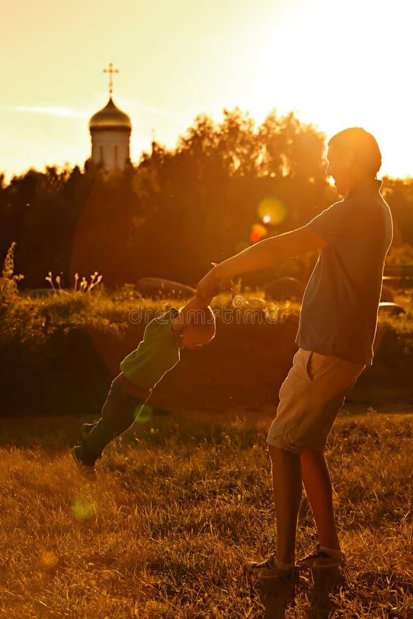 Szczęśliwy tata bawić się z jego synem w parku na tle kościół obrazy royalty free