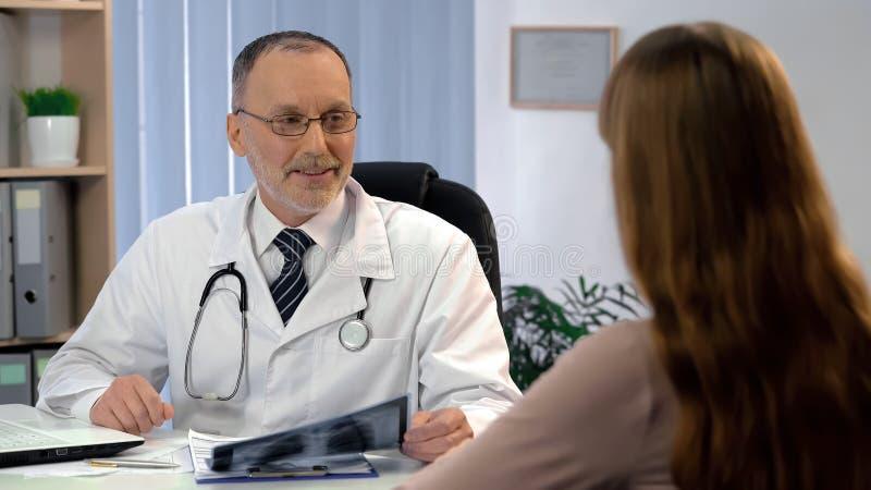 Szczęśliwy terapeuta mówi cierpliwego dobre wieści o wyzdrowieniu, trzyma płuca promieniowanie rentgenowskie fotografia stock
