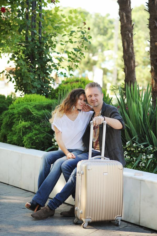 Szczęśliwy turysta miłości pary opowiadać plenerowy, obsiadanie na ławce w miasto parku zdjęcie royalty free