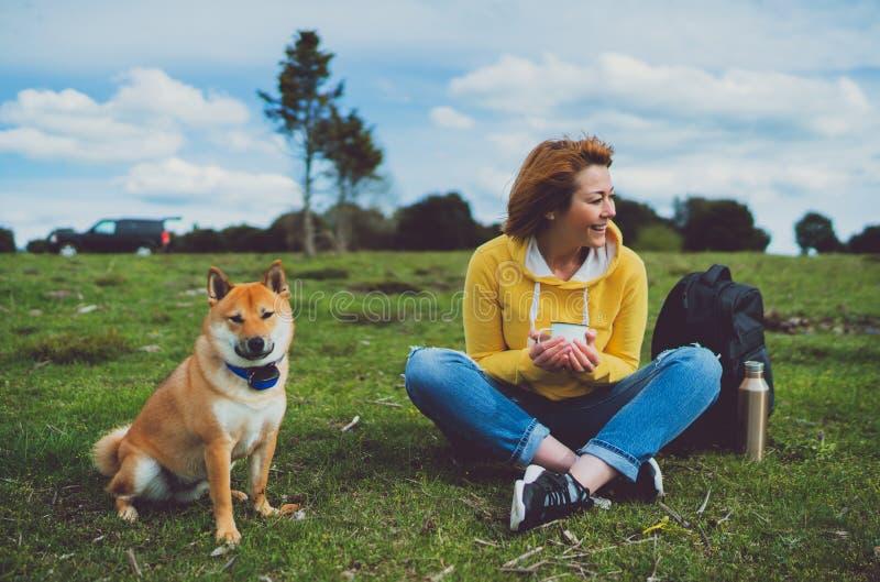 Szczęśliwy uśmiech dziewczyny mienie w ręki filiżanki napoju, czerwony japończyka psa shiba inu na zielonej trawie w outdoors nat fotografia royalty free