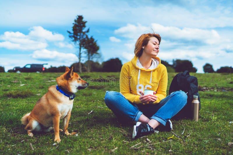 Szczęśliwy uśmiech dziewczyny mienie w ręki filiżanki napoju, czerwony japończyka psa shiba inu na zielonej trawie w outdoors nat fotografia stock