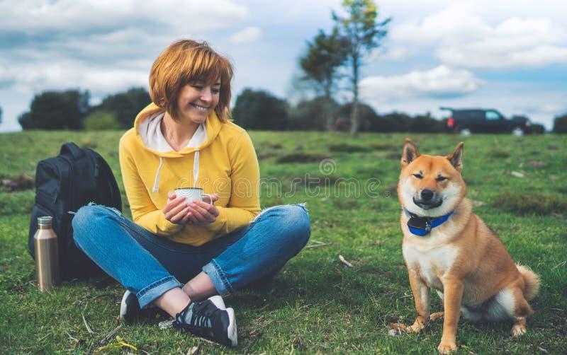 Szczęśliwy uśmiech dziewczyny mienie w ręki filiżanki napoju, czerwony japończyka psa shiba inu na zielonej trawie w outdoors nat zdjęcia royalty free
