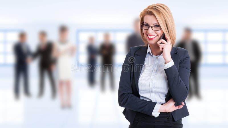 Szczęśliwy uśmiechnięty żeński business manager opowiada na telefonie obraz stock