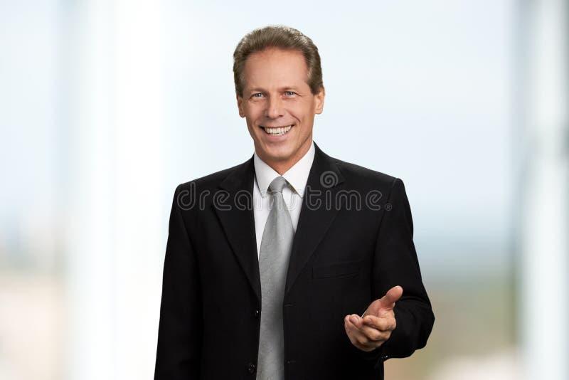 Szczęśliwy uśmiechnięty biznesmen gestykuluje z ręką obrazy stock