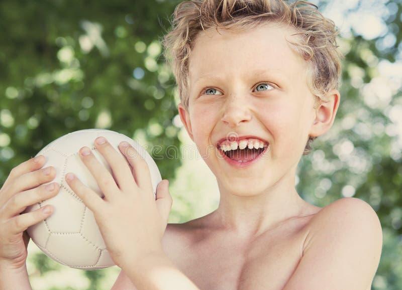 Szczęśliwy uśmiechnięty chłopiec lata portret z piłką fotografia stock