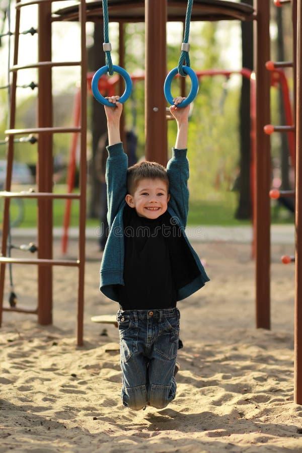 Szczęśliwy uśmiechnięty chłopiec obwieszenie na gimnastycznych pierścionkach na plenerowym boisku Szczery portret zdjęcie stock