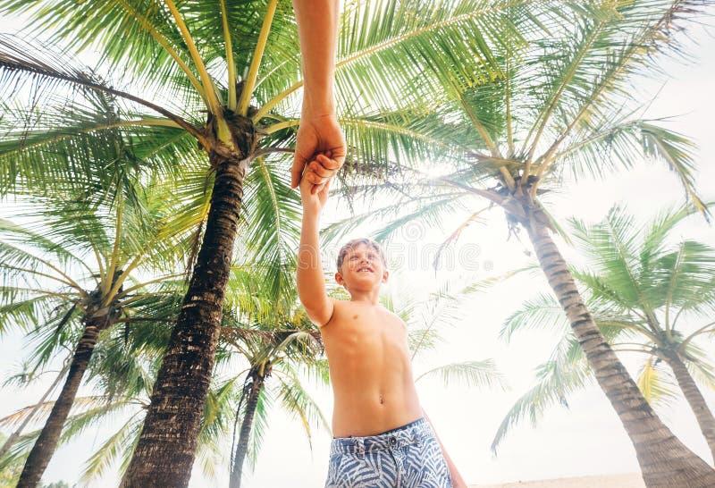 Szczęśliwy uśmiechnięty chłopiec wp8lywy dla ręki jego ojciec pod drzewkami palmowymi obrazy royalty free