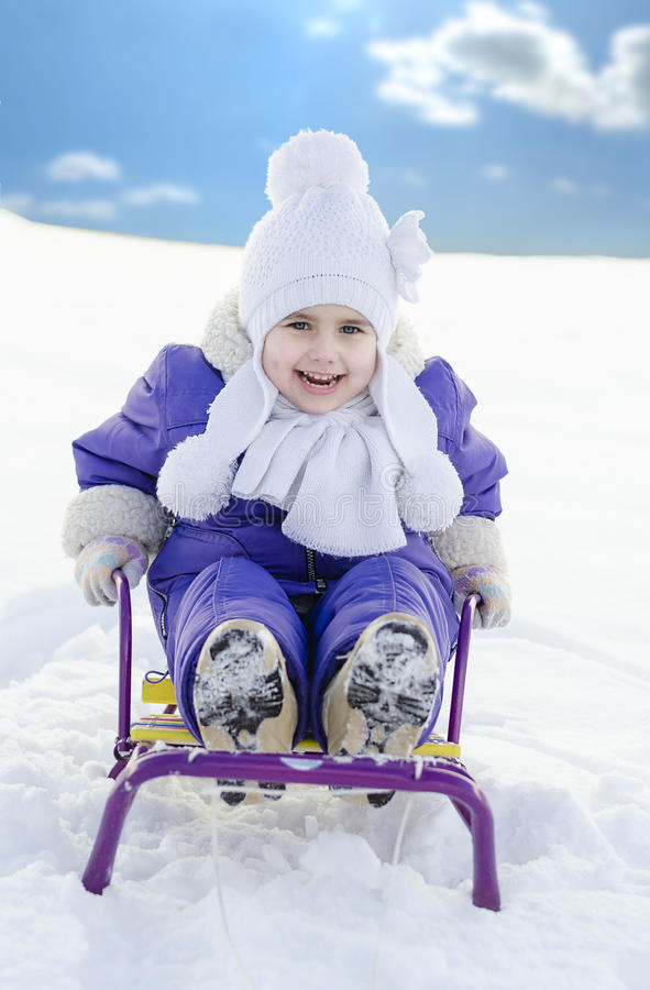 Szczęśliwy uśmiechnięty dziecko, chłopiec lub dziewczyna saneczkuje w świeżym śniegu w wint, obraz stock