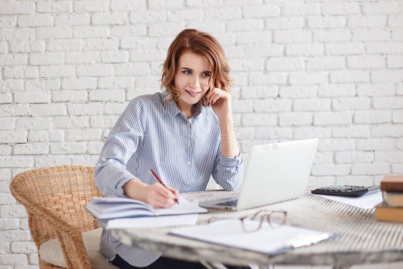 Szczęśliwy uśmiechnięty kobiety freelancer pisze notatkach w dzienniczka obsiadaniu w biurze lub w domu obrazy stock