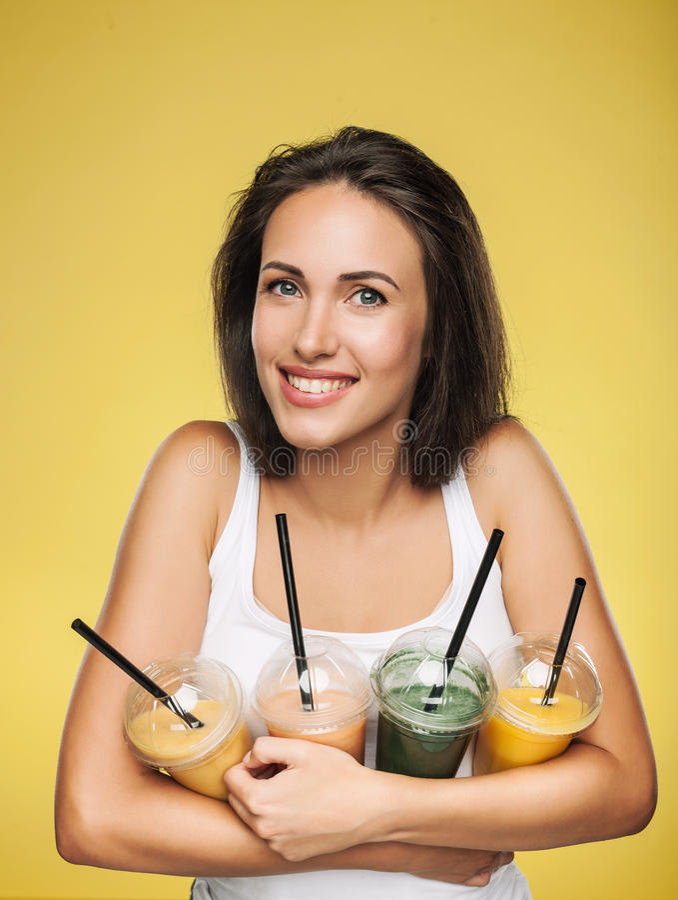 Szczęśliwy uśmiechnięty kobiety mienia smoothie zdjęcia royalty free