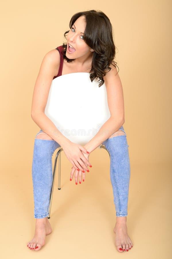 Szczęśliwy Uśmiechnięty młodej kobiety obsiadanie w Biały krzesła Relaksować fotografia royalty free