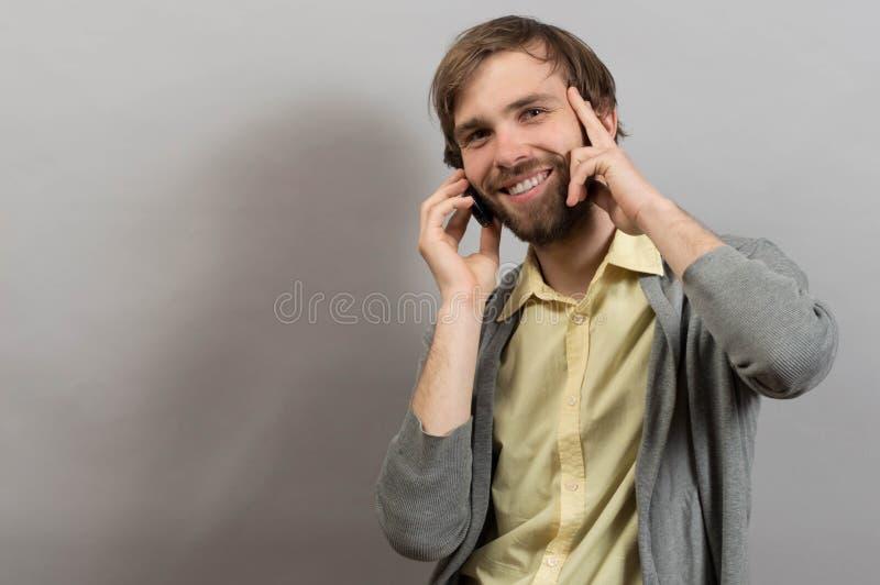 Szczęśliwy uśmiechnięty młody człowiek opowiada na wiszącej ozdobie odizolowywającej na popielatym obrazy stock