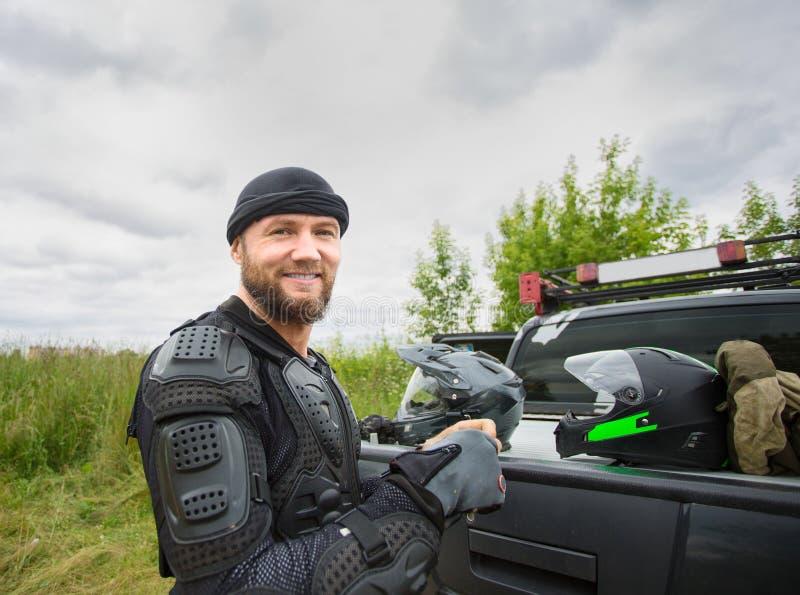 Szczęśliwy uśmiechnięty młody człowiek outdoors jest ubranym motocyklu kibel i przekładnię obraz stock