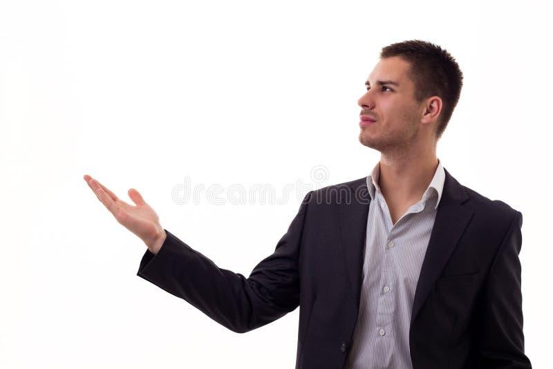 Szczęśliwy uśmiechnięty młody człowiek przedstawia twój produkt i pokazuje tekst lub fotografia royalty free