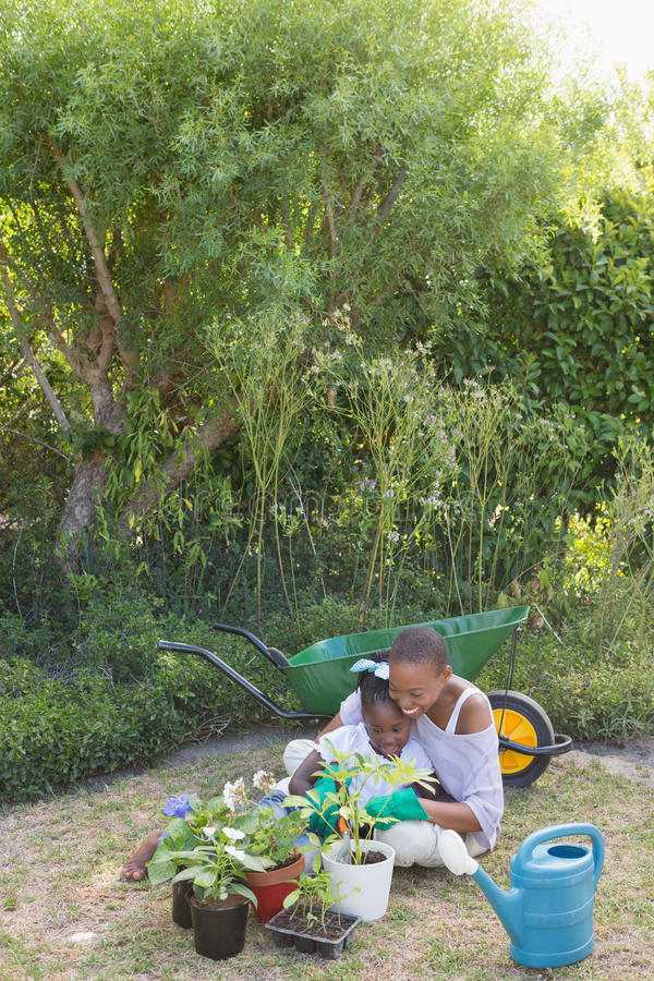 Szczęśliwy uśmiechnięty macierzysty ogrodnictwo z jej córką fotografia stock