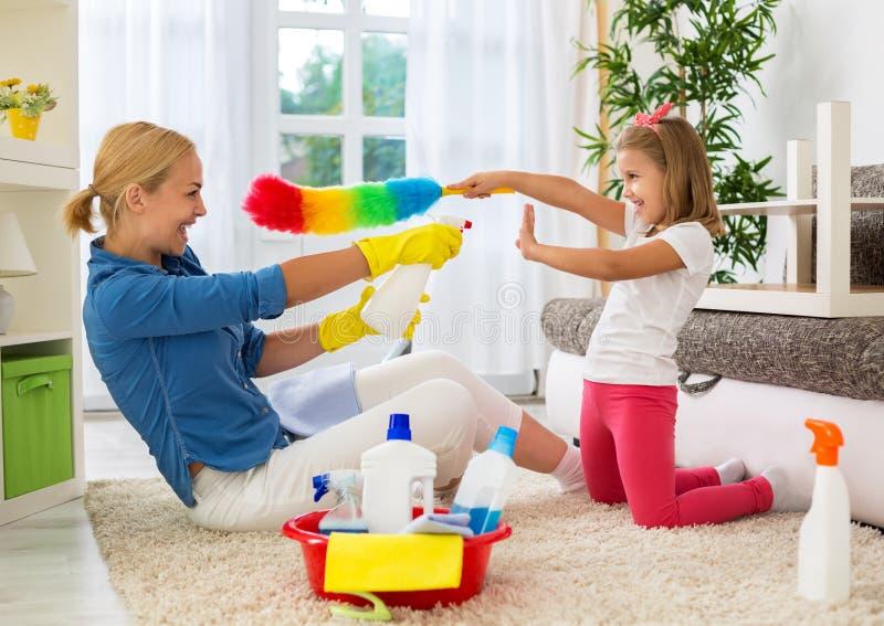 Szczęśliwy uśmiechnięty mamy i dzieciaka cleaning pokój fotografia royalty free