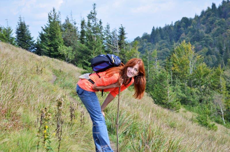Szczęśliwy uśmiechnięty miedzianowłosy dziewczyna wycieczkowicz z plecakiem i kijem w górach lesie i, męczyć odpoczywać i garbić  zdjęcia stock