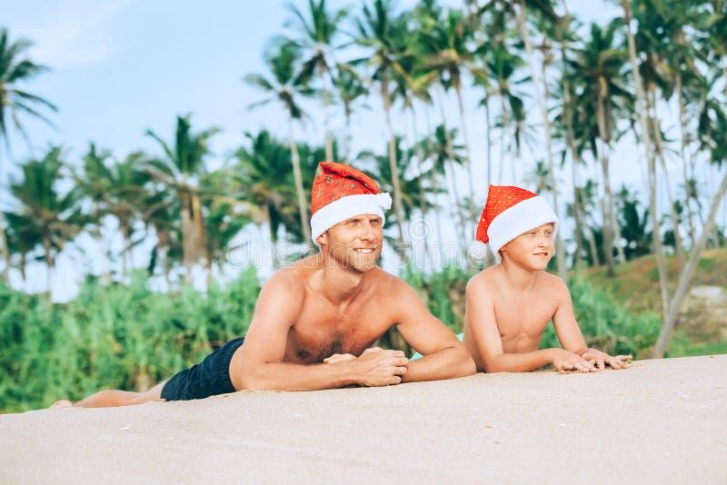 Szczęśliwy uśmiechnięty ojciec i syn w Santa kapeluszach słońca skąpanie na piasku zdjęcia stock
